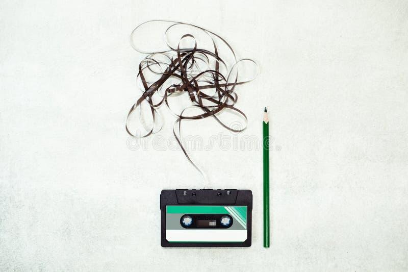 在白色背景的盒式磁带与被缠结的丝带 库存照片