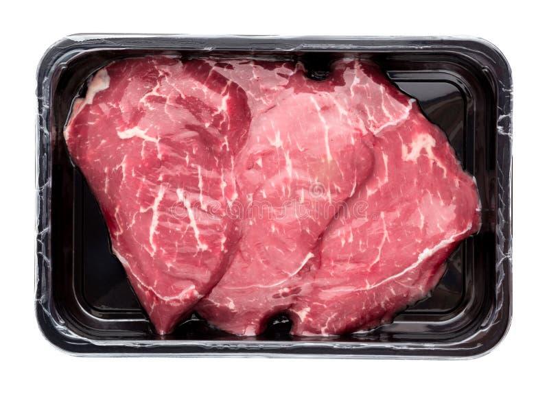 在白色背景的真空包装的牛肉 免版税库存图片