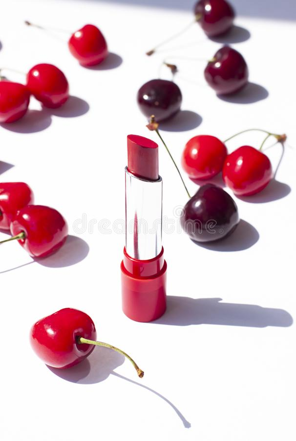 在白色背景的红色口红用成熟樱桃 免版税库存图片