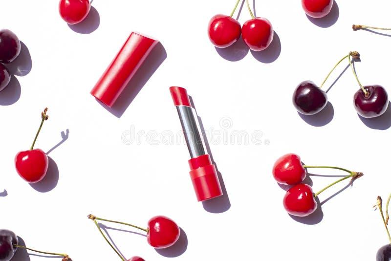 在白色背景的红色口红用成熟樱桃 免版税图库摄影