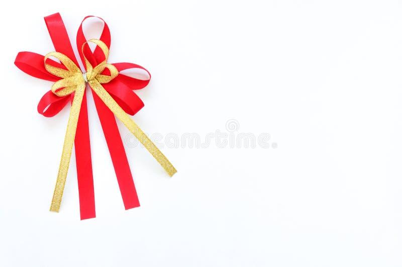 在白色背景的红色和金缎弓丝带 库存照片