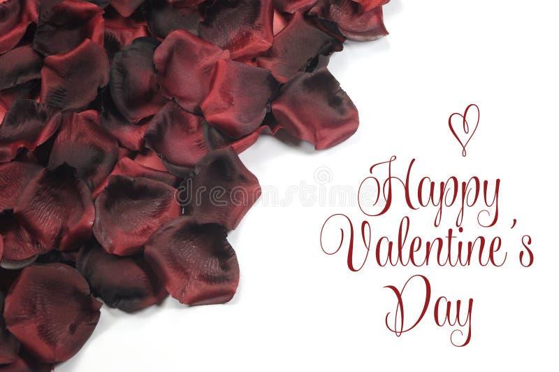在白色背景的红色玫瑰花瓣与愉快的情人节问候 免版税库存图片