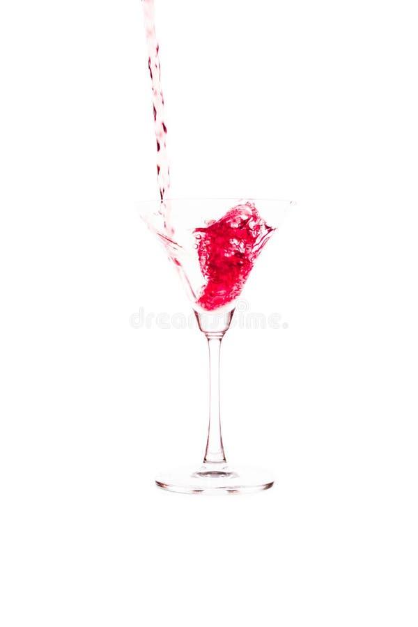 在白色背景的红葡萄酒倾吐的酒杯 库存图片