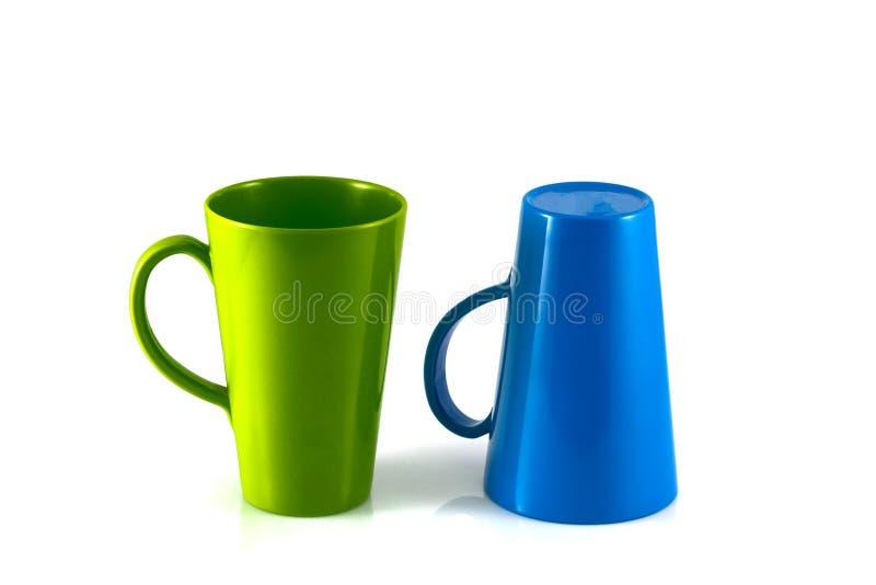 在白色背景的绿色和蓝色杯子孤立 免版税库存图片