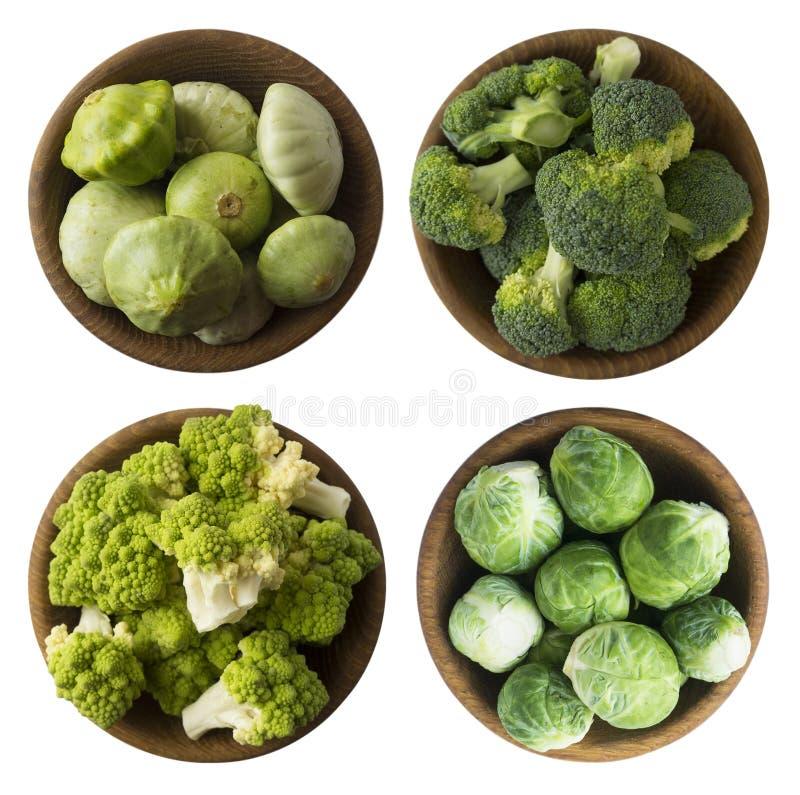 在白色背景的绿色食物 Brocoli、罗马花椰菜、在一个木碗的南瓜和抱子甘蓝圆白菜 免版税库存图片