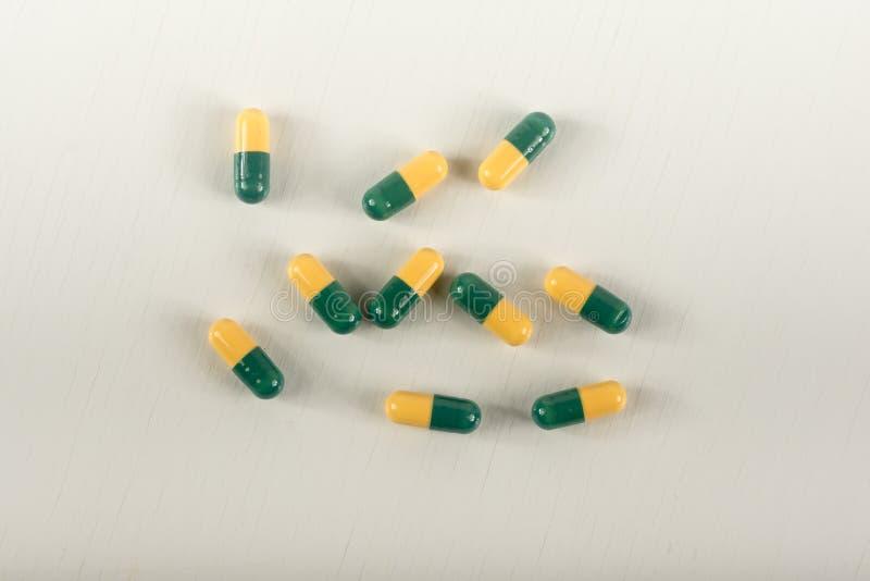 在白色背景的绿色,黄色tramadol胶囊药片 止痛药胶囊叫 免版税库存图片