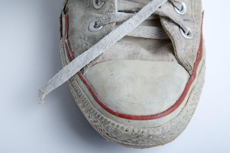 在白色背景的老和肮脏的运动鞋 免版税库存图片