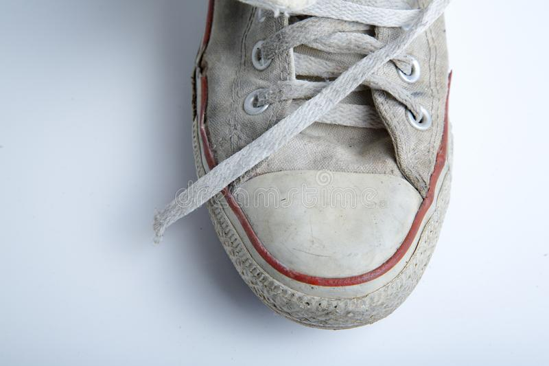 在白色背景的老和肮脏的运动鞋 免版税图库摄影
