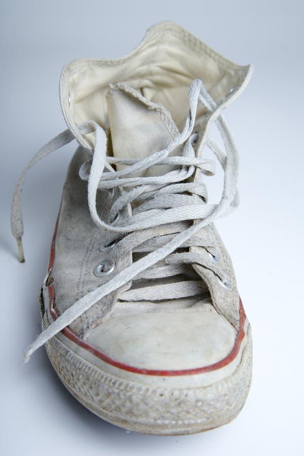 在白色背景的老和肮脏的运动鞋 图库摄影