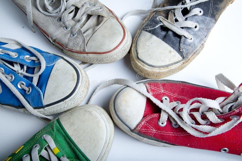 在白色背景的老和肮脏的运动鞋 库存图片