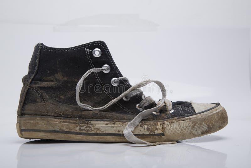 在白色背景的老和肮脏的运动鞋 免版税库存照片