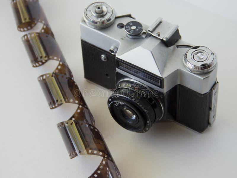 在白色背景的老照相机与影片 库存照片