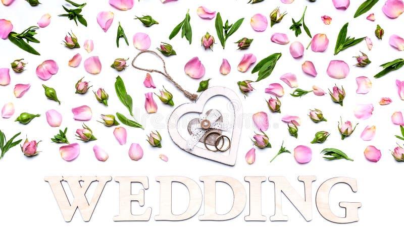 在白色背景的花纹花样 玫瑰的瓣和芽 在中心是圆环的一个立场以心脏的形式 ? 库存照片