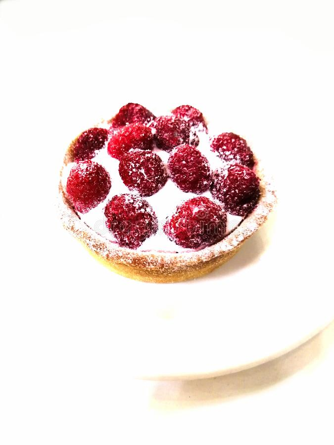 在白色背景的莓蛋糕在一块白色板材 免版税库存照片