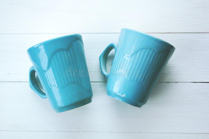 在白色背景的蓝色杯子 库存图片