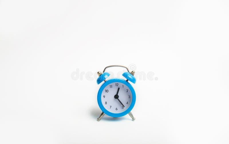 在白色背景的蓝色闹钟第一次表明管理起点  时间,对a的时间流程的概念  免版税库存图片