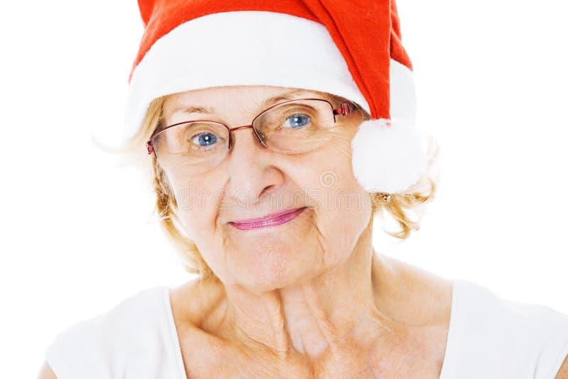 戴在白色背景的资深妇女圣诞老人帽子 免版税图库摄影