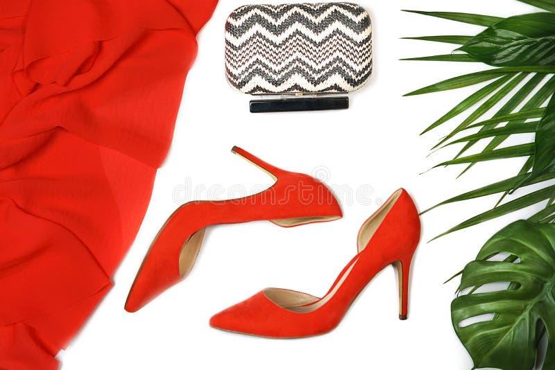 在白色背景的顶视图党成套装备构成红色鞋子辅助部件首饰传动器热带叶子,被隔绝 免版税图库摄影