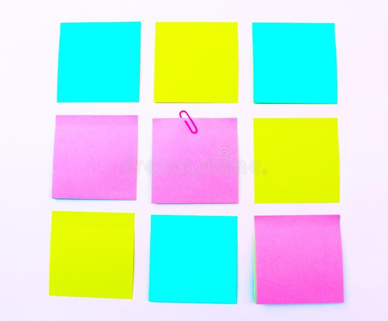 在白色背景的黄色,桃红色,蓝色稠粘的笔记孤立 图库摄影