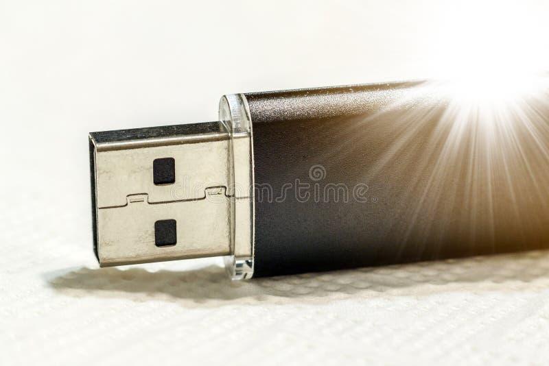 在白色背景的黑usb闪光驱动与太阳射线 库存照片