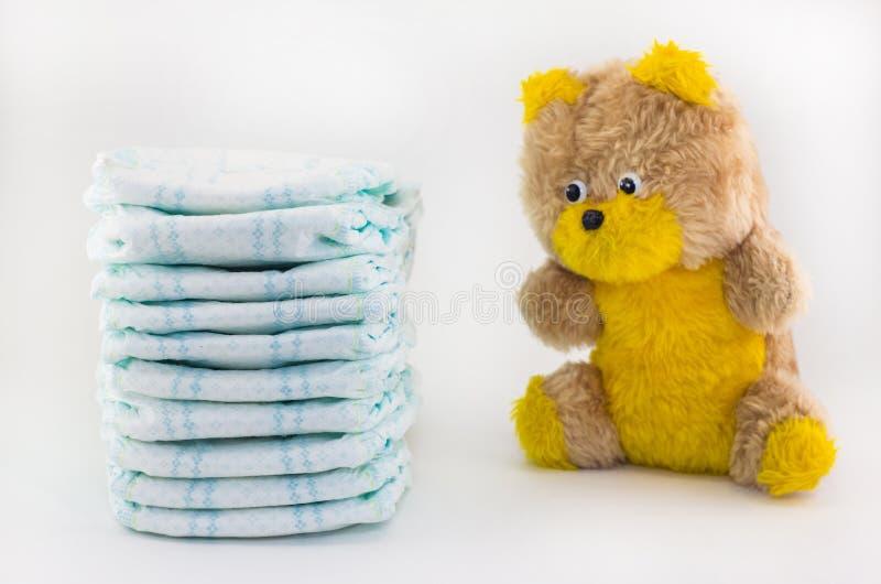 在白色背景的Pampers和婴孩戏弄小熊,熊 免版税库存图片