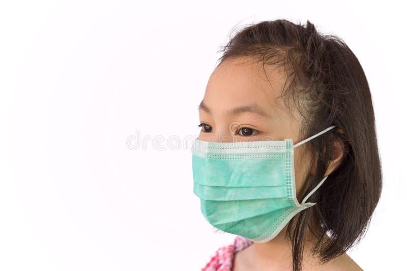 在白色背景隔绝的一个医疗面具的画象亚裔女孩,戴着卫生面具,流行病的概念的孩子, 库存图片