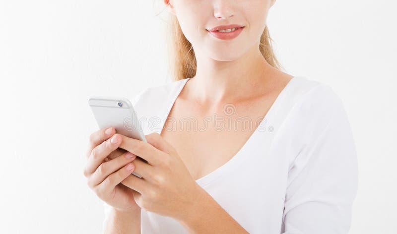 在白色背景隔绝的一个微笑的年轻女人藏品手机的播种的画象,聊天的女孩,广告概念 免版税库存图片