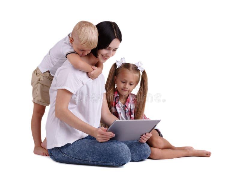 在白色背景隔绝的一个愉快的家庭 有她的拿着膝上型计算机和看它的小孩的一个微笑的母亲 图库摄影