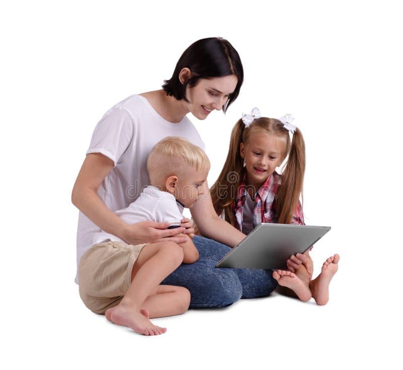 在白色背景隔绝的一个愉快的家庭 有她的拿着膝上型计算机和看它的小孩的一个微笑的母亲 免版税图库摄影