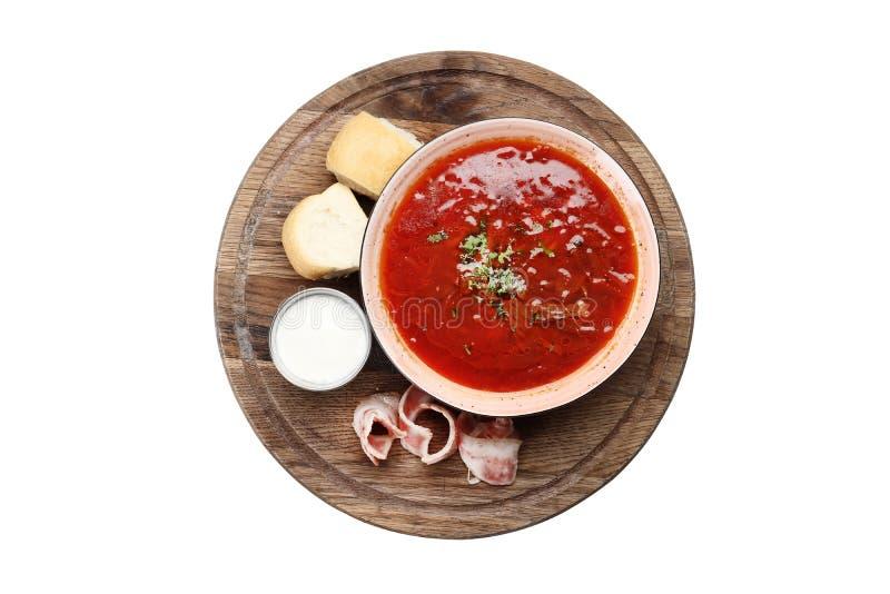 在白色背景隔绝的一个木板的罗宋汤用烟肉和pampushkas 免版税库存照片