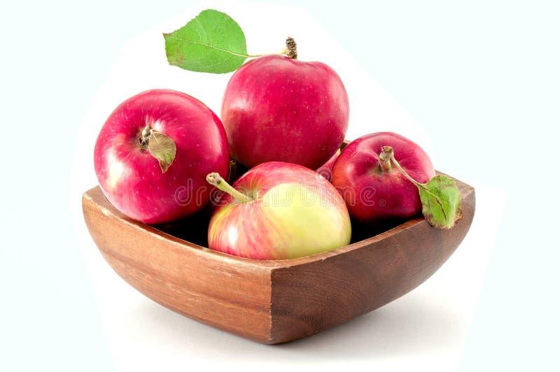在白色背景隔绝的一个棕色木碗的有机呈杂色的红色苹果 免版税图库摄影
