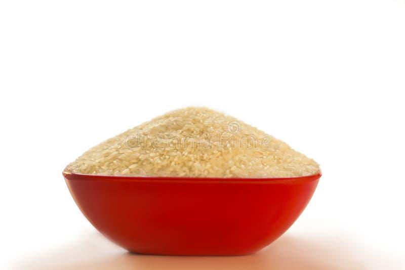 在白色背景隔绝的一个红色碗的未煮过的米 库存照片