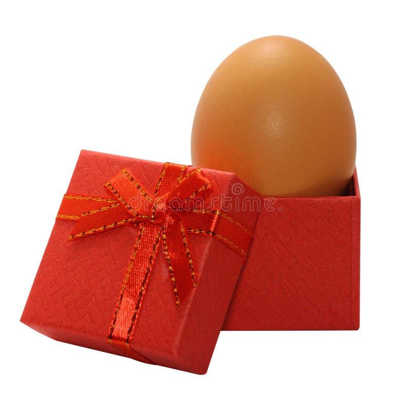 在白色背景隔绝的一个红色纸板箱的未加工的鸡鸡蛋 鸡蛋关闭看法 图库摄影