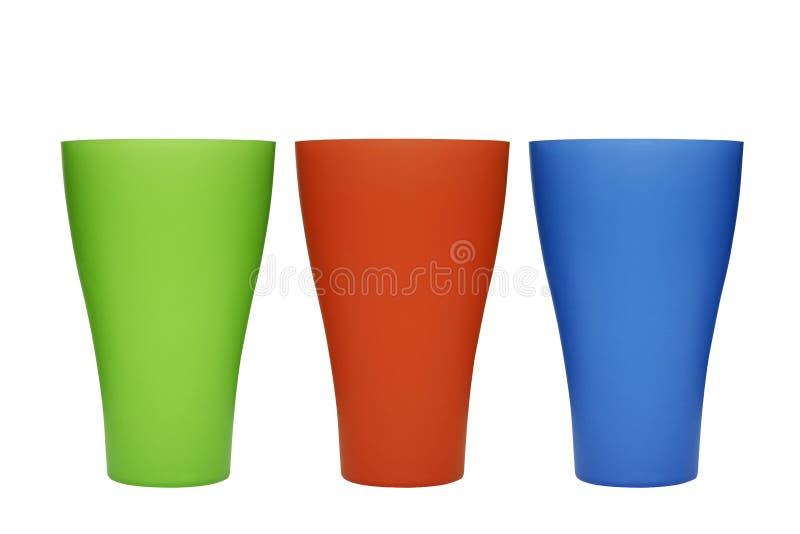 在白色背景隔绝的三块塑料多彩多姿的玻璃 在白色背景隔绝的各种各样的颜色塑料玻璃 免版税库存照片