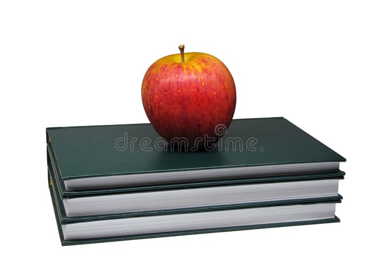 在白色背景隔绝的三本绿色精装书顶部的红色苹果 库存图片