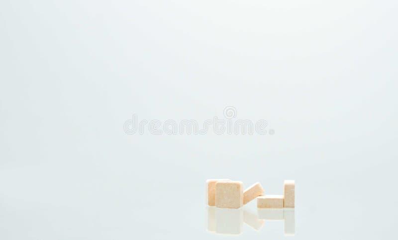 在白色背景隔绝的五个橙色正方形片剂药片 库存图片