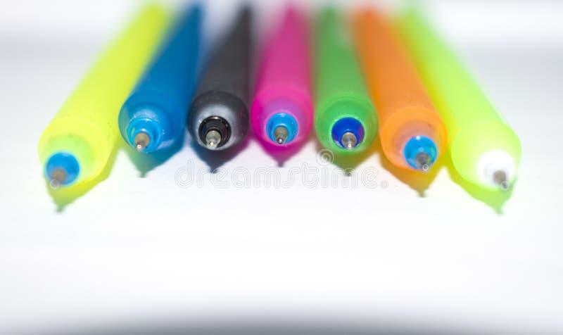在白色背景隔绝的五颜六色的笔咬事务 库存照片