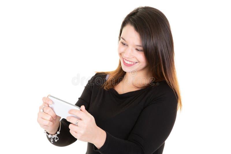 在白色背景隔绝的偶然年轻女人身分看殷勤地电话浏览网页屏幕和微笑 免版税库存照片