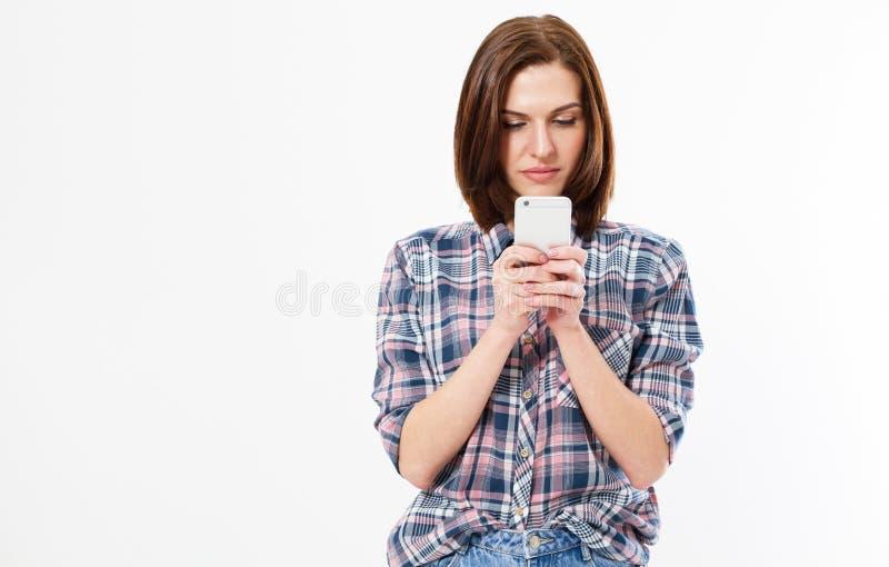 在白色背景隔绝的偶然穿戴的欧洲女孩身分特写镜头照片看殷勤地手机屏幕, 图库摄影