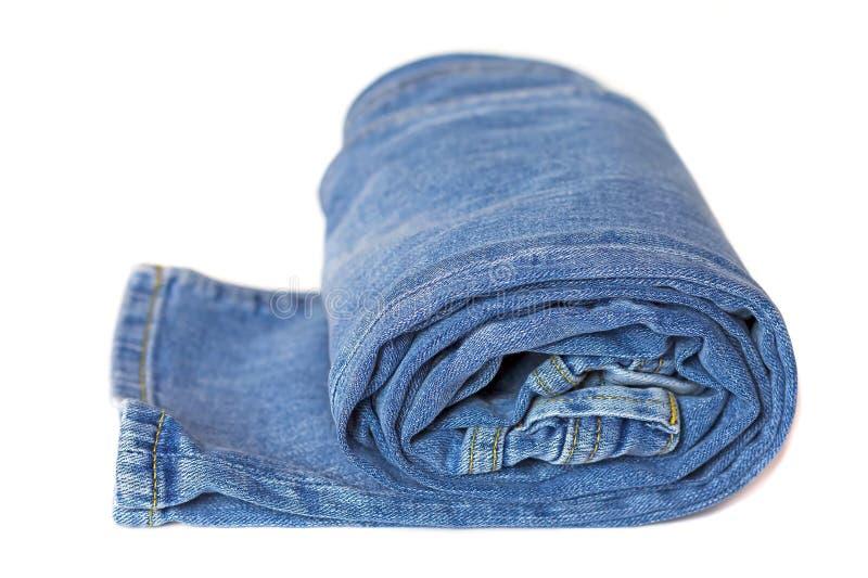 在白色背景隔绝的卷牛仔裤 库存照片