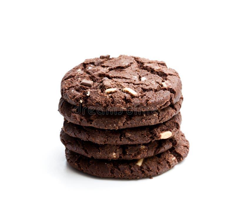 在白色背景隔绝的堆黑暗的巧克力曲奇饼 库存照片