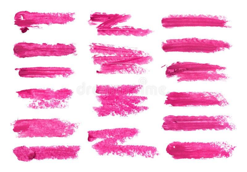 在白色背景隔绝的大套紫红色的唇膏污点 被弄脏的构成产品样品 库存图片