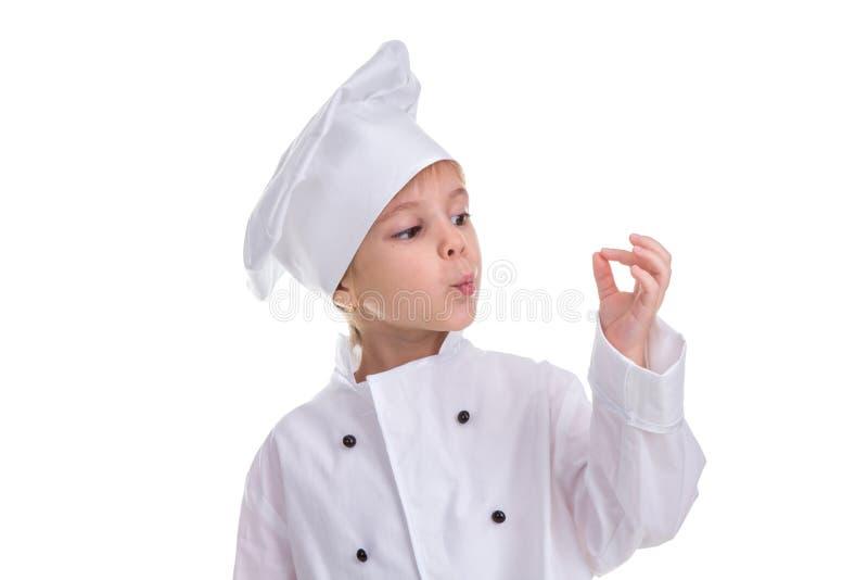 在白色背景隔绝的女孩厨师白色制服,吹对手指,好标志 风景图象 库存图片