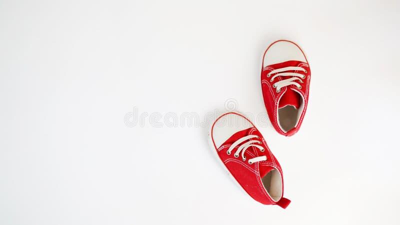在白色背景隔绝的婴孩红色运动鞋 ?? 免版税库存图片