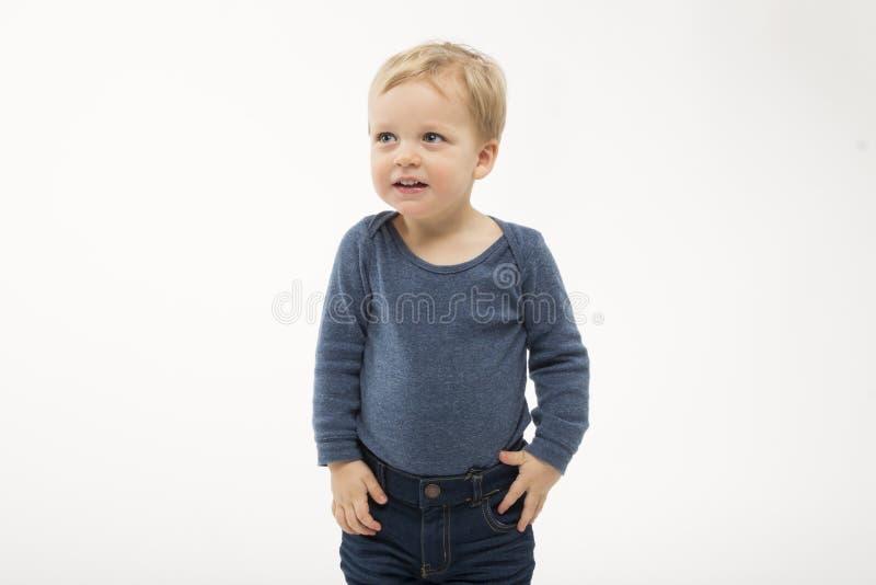 在白色背景隔绝的害羞的男婴 有要求的面孔表示逗人喜爱的小孩 可爱孩子要求什么去 库存照片