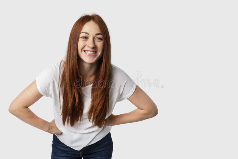 在白色背景隔绝的年轻可爱的红头发人妇女画象站立用两手插腰她的手,倾斜和微笑 免版税库存照片