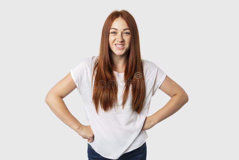 在白色背景隔绝的年轻可爱的红头发人妇女画象站立用两手插腰她的手,皱眉和显示牙 免版税库存照片