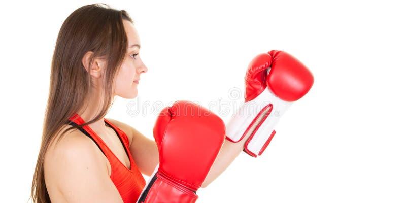 在白色背景隔绝的年轻女人戴着解决与箱子有氧运动的红色拳击手套心脏 免版税图库摄影