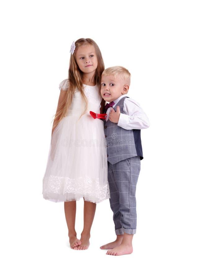在白色背景隔绝的弟弟和姐妹 逗人喜爱的一起站立男孩和的女孩 闩上构成概念系列螺母 图库摄影