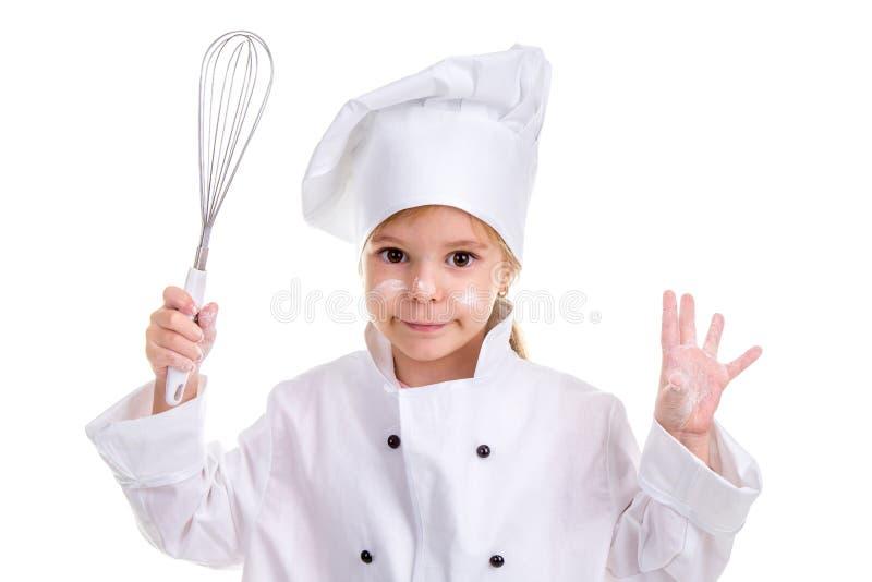 在白色背景隔绝的微笑的女孩厨师白色制服 被撒粉于的面孔 在一只手和别的上拿着飞奔 图库摄影
